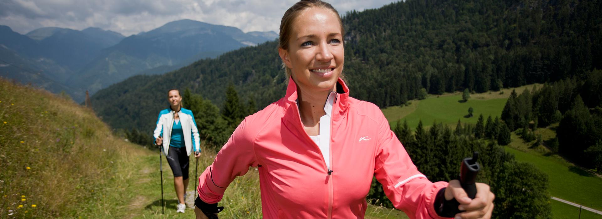 zwei Frauen, die Nordic Walking in den Bergen genießen