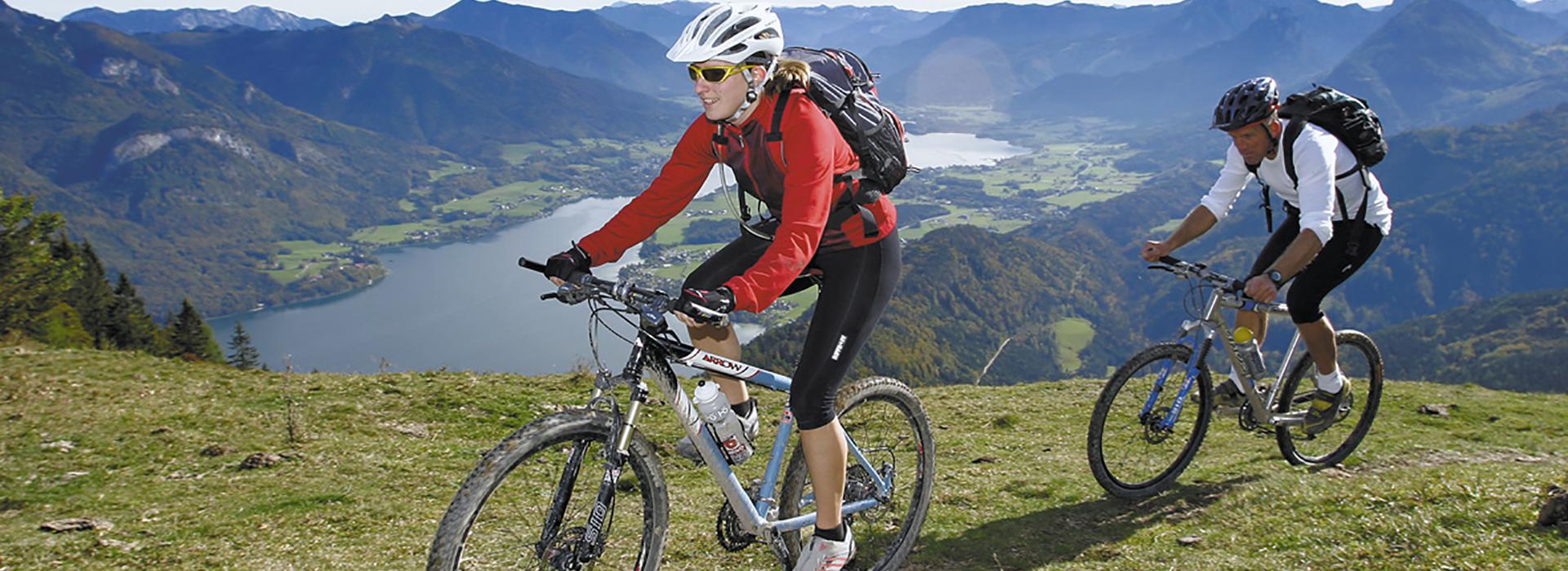 2 Mountainbiker genießen die Berge und die Natur über einem wunderschönen See